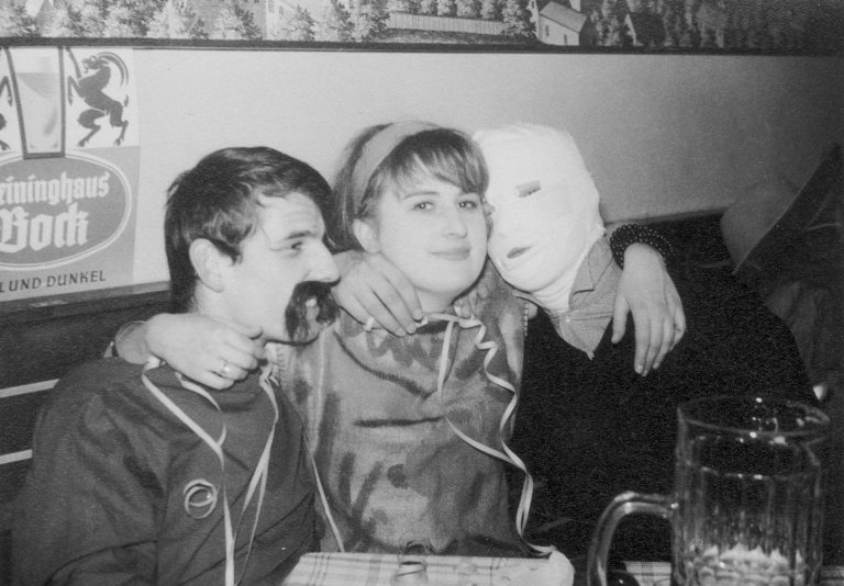 """Maskenball im """"Brandhof"""" Anfang der 1960er-Jahre. Elisabeth Wondrak (Kunstakademie), """"Mumie"""" Günther Schmidt-Corten (evang. Jugend) und Meinrad Nell. Im Vordergrund ausnahmsweise ein ganz """"normaler"""" Bierkrug."""
