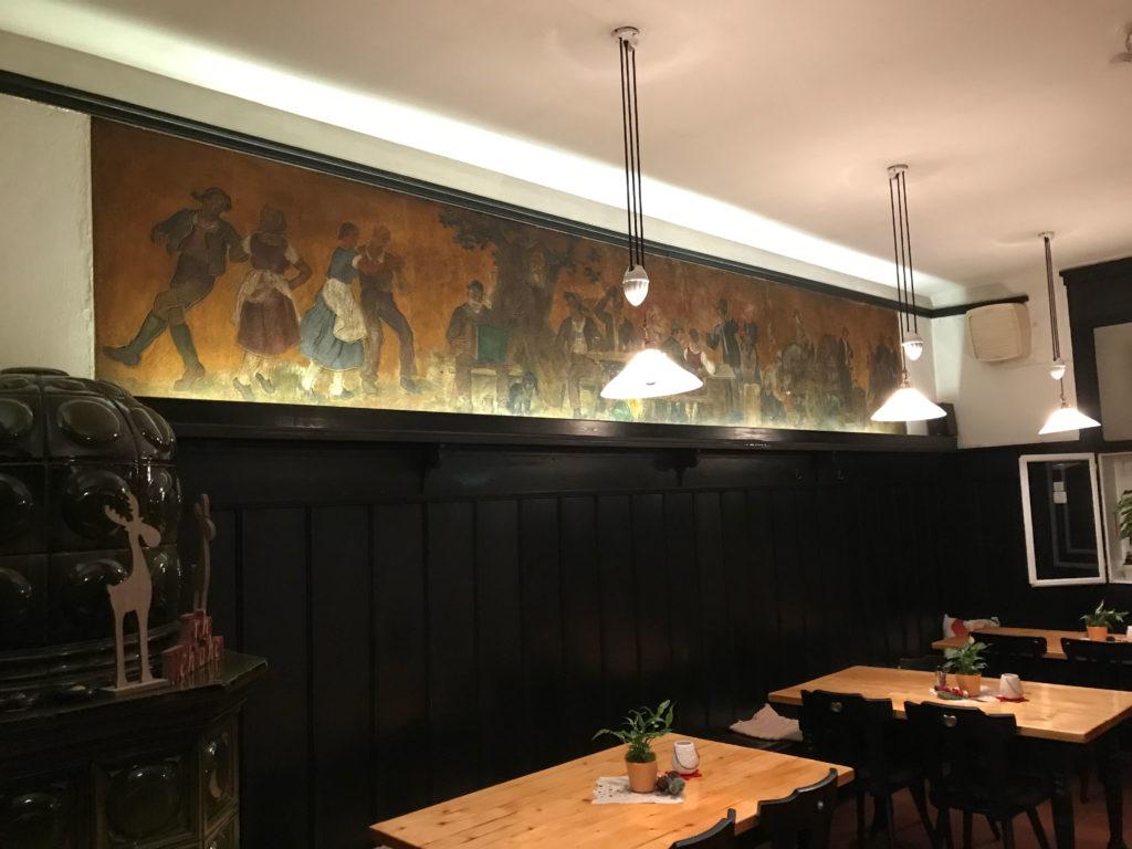 """Die """"Lobisser-Stubn"""" des ehemaligen """"Scanzoni"""". Original-Fresken von Switbert Lobisser. In diesem Umfeld fand ich mein zweites Zuhause in Klagenfurt. Beinahe unverändert wurde es erhalten. Sogar die Sitzordnung blieb großteils original. Der Kachelofen links strahlte gesunde wohltuende kuschelige Wärme."""